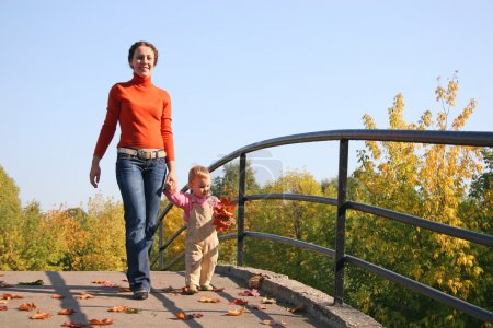 Mother with baby walk on bridge autumn