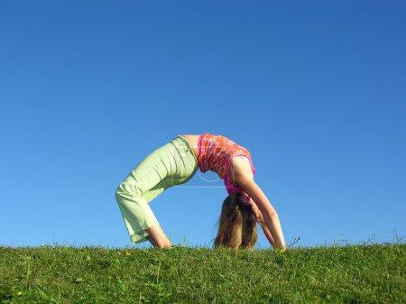 Girl as bridge on grass