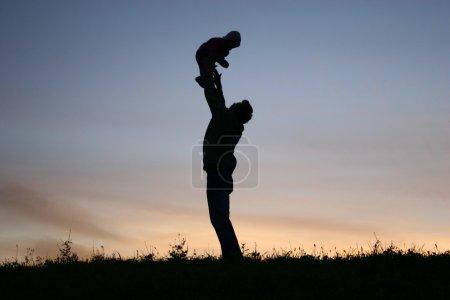 Photo pour Père de silhouette avec bébé - image libre de droit
