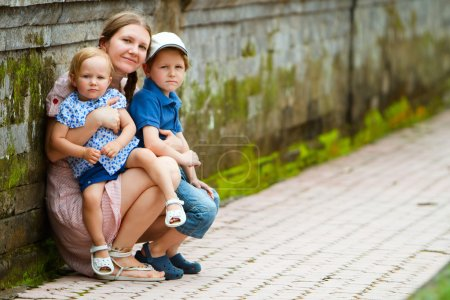 Photo for Portrait of young beautiful woman and her two kids outdoors - Royalty Free Image