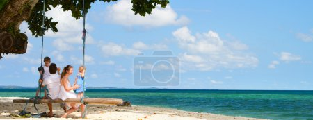 Photo for Panoramic photo of family of four having fun on tropical beach - Royalty Free Image