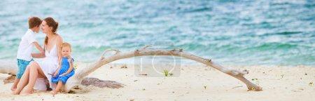 Photo pour Photo panoramique de la belle jeune femme avec deux enfants assis sur la plage tropicale - image libre de droit