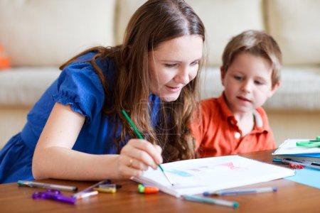 Photo pour La jeune mère et ses deux enfants dessinent ensemble. Peut également être utilisé dans le contexte de la maternelle / garderie - image libre de droit