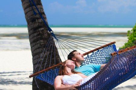 Photo pour Jeune couple romantique relaxant dans un hamac sur la plage tropicale de l'île de Zanzibar - image libre de droit