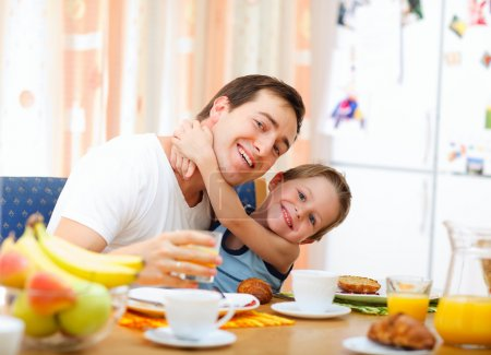 Photo for Young happy father and son having breakfast together - Royalty Free Image