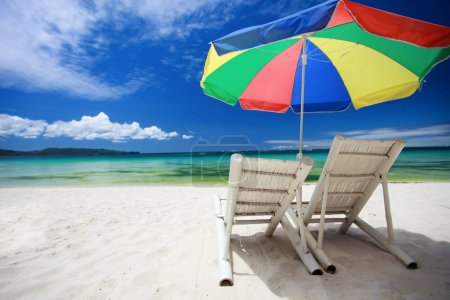 Two beach chairs and colorful umbrella