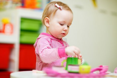 Photo for Adorable toddler girl playing with toys at home or daycare place - Royalty Free Image