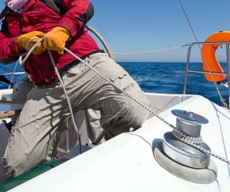 Photo pour Homme tenant la corde sur le bateau à voile - image libre de droit
