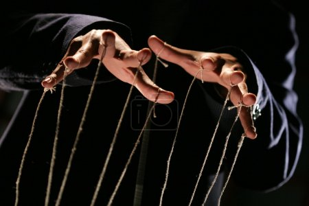 Conceptual series: hands of puppeteer with rope...
