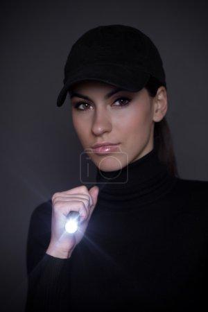 Photo pour Femme avec lampe de poche dans l'obscurité - image libre de droit