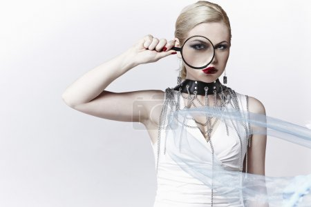 Serious blonde in a retro style with a magnifier i...
