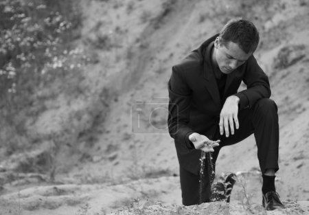 Man in elegant suit in open-cast mine.