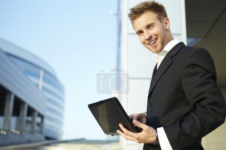Closeup portrait of a happy young businessman using laptop on street