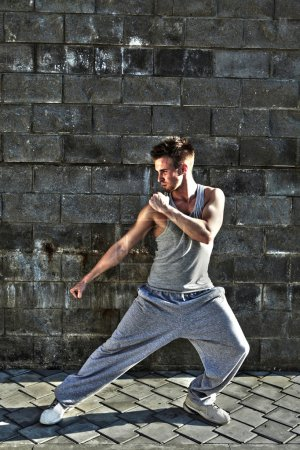 Young attractive man dancing in urban background
