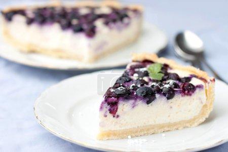 Photo pour Assiettes avec gâteau au fromage aux baies sur nappe lilas - image libre de droit