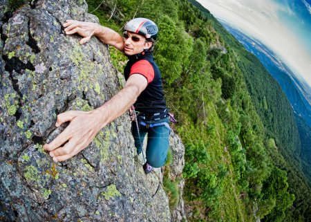 Photo for Young white man climbing a steep wall in mountain, rock-climb extreme sport, summer season. Horizontal orientation - Royalty Free Image