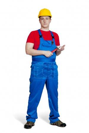 Photo pour Le travailleur en uniforme et casque avec une clé. isolé sur blanc. - image libre de droit