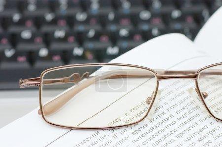 Photo pour Lunettes et livres sur l'ordinateur portable - image libre de droit
