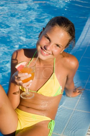 The girl with a cocktail at pool
