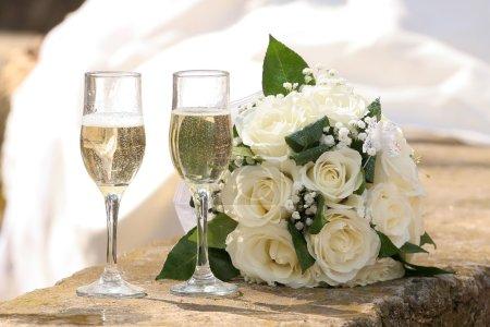 Photo pour Deux verres de mariage avec champagne et un bouquet de roses blanches - image libre de droit