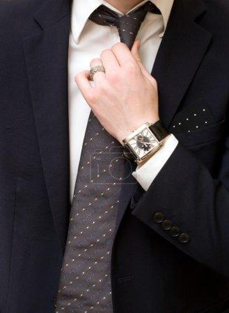 Young man in suit, tie a necktie