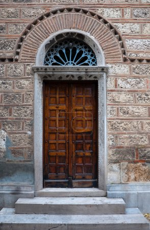 Old door of Greek temple with arch