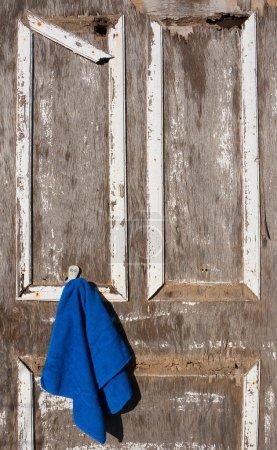 Old broken door with a blue towel