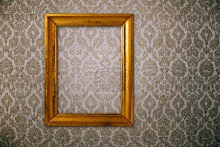 Gold frame over vintage wallpaper