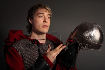 Thoughtful knight holds a helmet