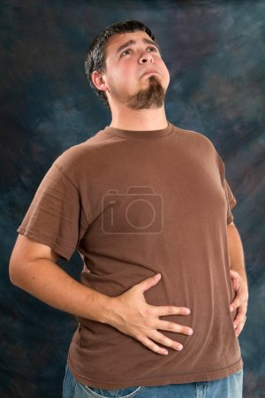 Overweight man holds his stomach after eating too ...