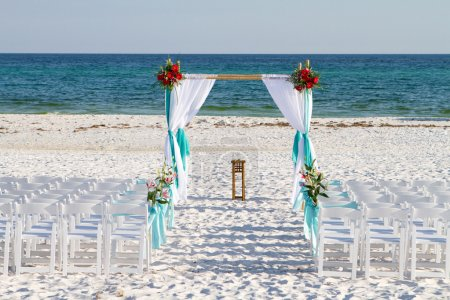 Photo for Wedding archway, chairs and flowers are arranged on the sand in preparation for a beach wedding ceremony. - Royalty Free Image