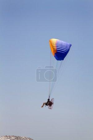 Photo pour Un homme pieds nus suspendu par un parapente motorisé survole une colline contre un ciel bleu . - image libre de droit
