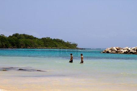 Photo pour Deux jeunes touristes hommes pataugent dans l'océan sur une plage en Jamaïque . - image libre de droit
