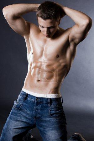 Photo pour Homme jeune bodybuilder sur fond noir - image libre de droit