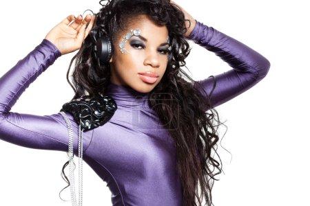 Mulatto girl DJ listens music with headphones