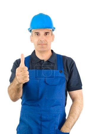 Foto de El trabajador en un overol azul y un casco azul muestra el dedo grande - Imagen libre de derechos
