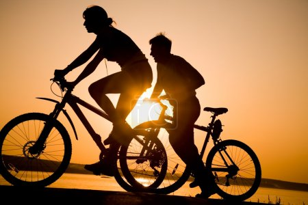 Photo for Image of sporty couple on bicycles outdoors against sunset. Silhouette. - Royalty Free Image
