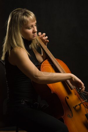 Photo pour Musicien de femme avec violoncelle sur fond foncé - image libre de droit