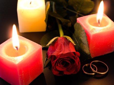 Photo pour Bagues d'or de mariage, rose et bougies dans la nuit - image libre de droit