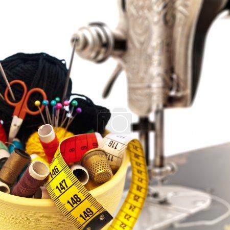 Foto de Tejer diferentes artículos en el recipiente contra la vieja máquina de coser - Imagen libre de derechos