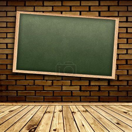 Photo pour Tableau noir de l'école vide au mur de briques à l'intérieur avec plancher en bois - image libre de droit