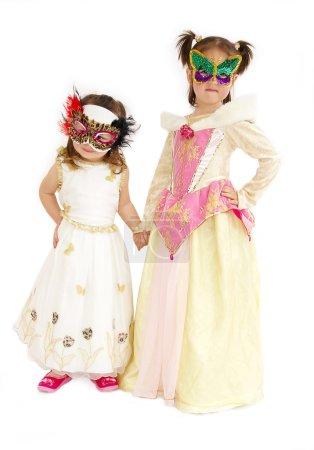 Photo pour Deux belles filles en costumes et masques sur fond blanc - image libre de droit