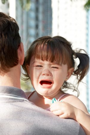 Photo for Young girl crying on her father's shoulder - Royalty Free Image