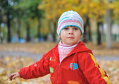 Portrait of the little girl in autumn forest