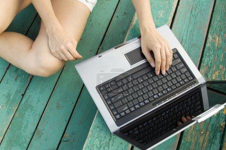 Photo pour Les mains et les pieds des femmes à côté de l'ordinateur portable sur un escalier en bois. Vue du dessus - image libre de droit