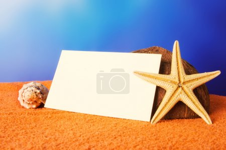 Holiday beach concept with shells, sea star and a blank postcard