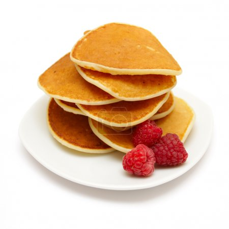 Small pancakes topped with berries isolated on whi...