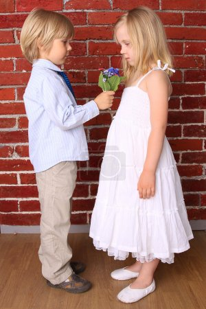Little boy gives a girl a beautiful bouquet of flowers. Love con