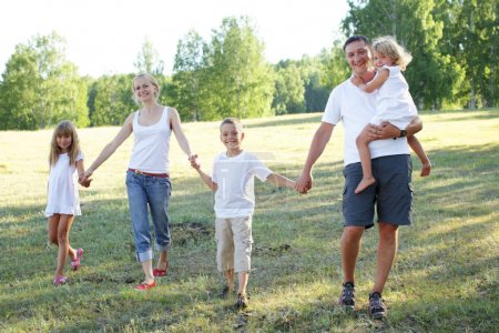 Photo for Happy family with three children walking on park - Royalty Free Image