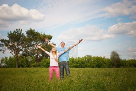 Photo for Couple standing on grass with raised arms. - Royalty Free Image